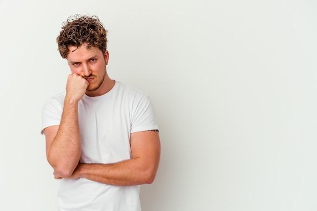 Молодой кавказский человек, изолированные на белом фоне, который чувствует себя грустным и задумчивым, глядя на пространство для копирования.