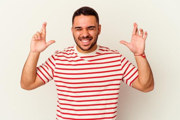 Молодой кавказский человек изолирован на белом, скрестив пальцы за удачу