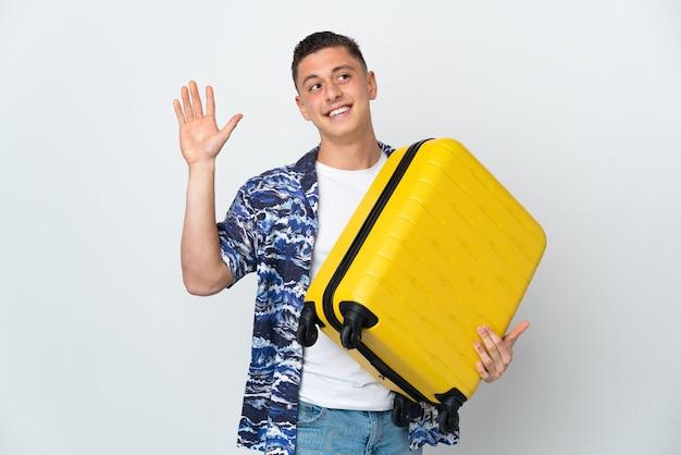 旅行スーツケースと敬礼で休暇中に白で隔離の若い白人男性