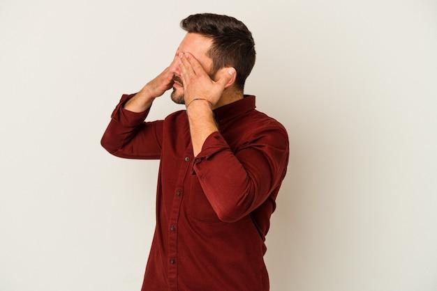 흰 벽에 고립 된 젊은 백인 남자 손으로 눈을 덮고 두려워.