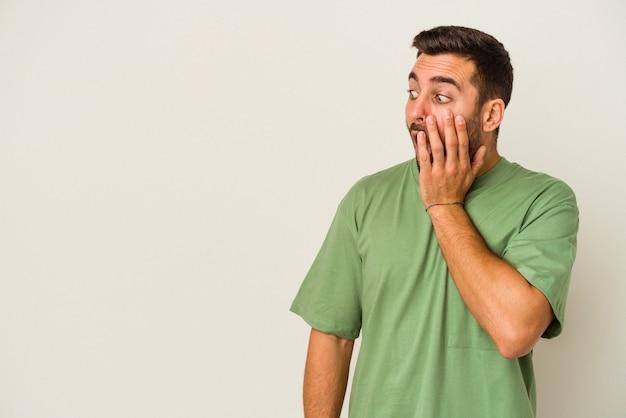 Молодой человек кавказской изолирован на белой стене шокирован из-за чего-то, что она видела.