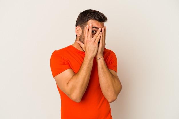 白い壁に孤立した若い白人男性は、怯えて神経質な指で瞬きします。