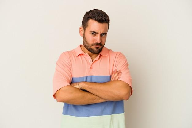 흰 벽에 고립 된 젊은 백인 남자는 뺨을 불면, 피곤 식. 표정 개념.