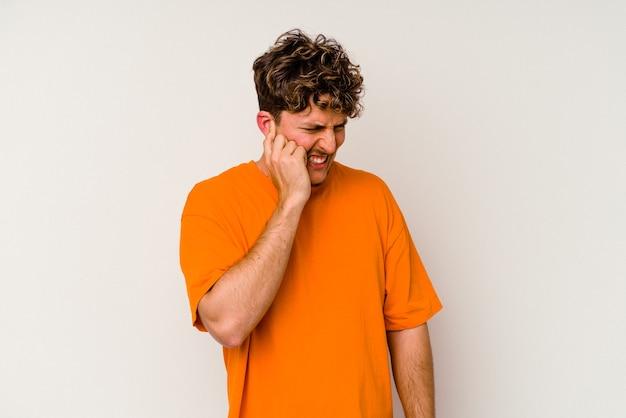 손으로 귀를 덮고 흰 벽에 고립 된 젊은 백인 남자.