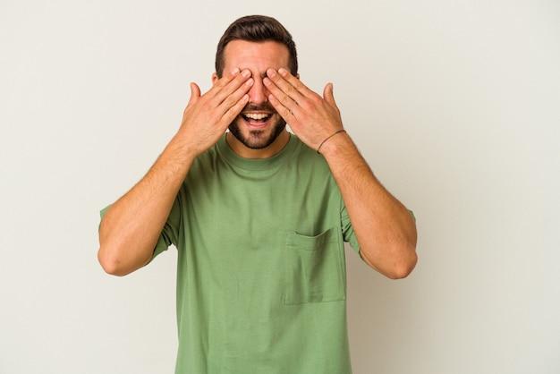 흰 벽에 고립 된 젊은 백인 남자는 손으로 눈을 다루고, 광범위하게 놀라움을 기다리고 있습니다.