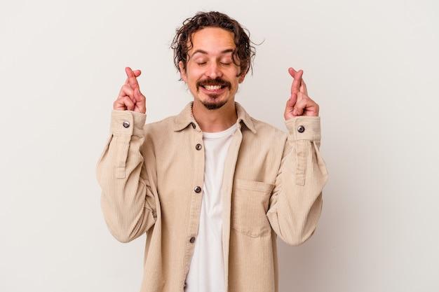 행운을 갖는 흰 벽 횡단 손가락에 고립 된 젊은 백인 남자