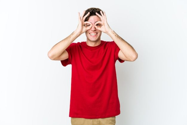 Молодой кавказский человек, изолированный на белой стене, взволнован, держа на глазах одобренный жест.
