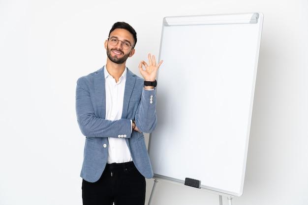 화이트 보드에 프레젠테이션을하고 손가락으로 확인 표시를 보여주는 흰 벽에 고립 된 젊은 백인 남자