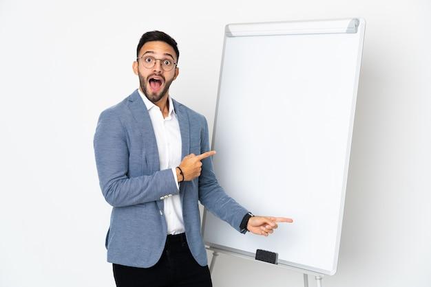 젊은 백인 남자는 화이트 보드에 프레젠테이션을 흰색 벽에 고립 된 측면을 가리키는 동안 놀란