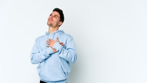 白い壁に分離された若い白人男性はフレンドリーな表情で、手のひらを胸に押し付けます。愛の概念。