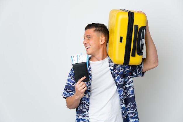 Молодой кавказский мужчина изолирован на белой стене в отпуске с чемоданом и паспортом