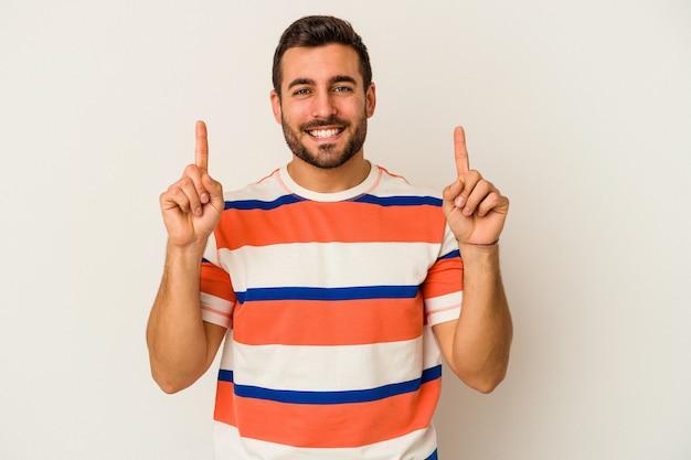 흰 벽에 고립 된 젊은 백인 남자는 빈 공간을 보여주는 두 앞 손가락으로 나타냅니다.