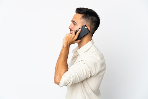 누군가와 휴대 전화로 대화를 유지하는 흰 벽에 고립 된 젊은 백인 남자
