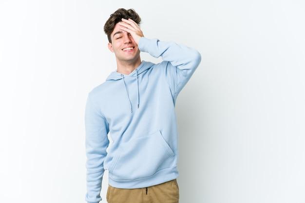 Молодой человек кавказской изолирован на белой стене смеется счастливыми, беззаботными, естественными эмоциями.