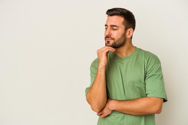 의심스럽고 회의적인 표정으로 옆으로 찾고 흰 벽에 고립 된 젊은 백인 남자.