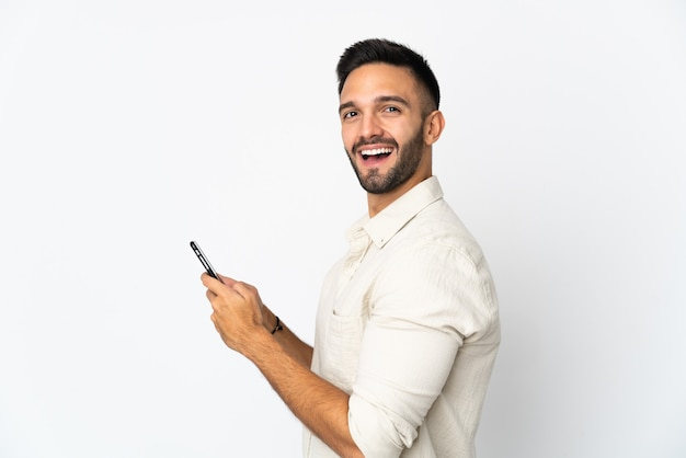 Молодой кавказский человек изолирован на белой стене, отправляя сообщение или электронное письмо с мобильного телефона
