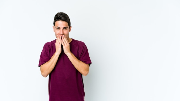 Молодой кавказский человек, изолированный на белой стене, потрясен, прикрывая рот руками, стремясь открыть для себя что-то новое.