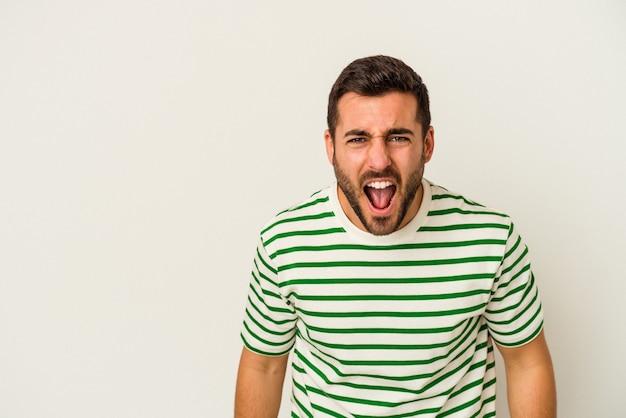 Молодой человек кавказской изолирован на белой стене кричит очень сердитый, концепция ярости, разочарование.
