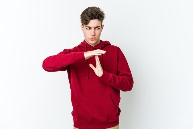 Молодой кавказский человек изолирован на белой стене показывая жест тайм-аута.