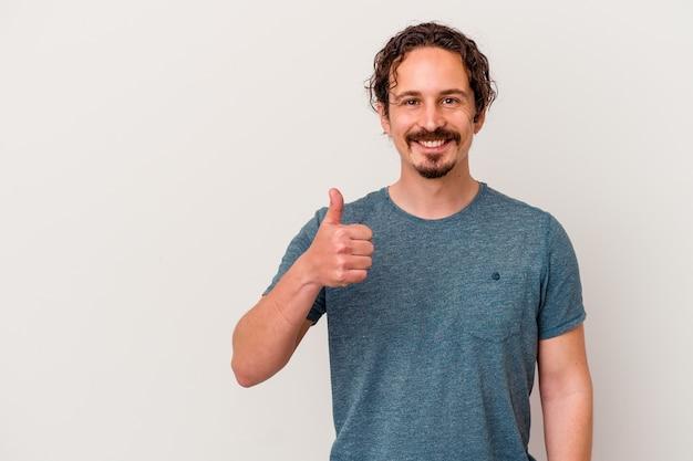 Молодой кавказский человек изолирован на белой стене, улыбаясь и поднимая палец вверх