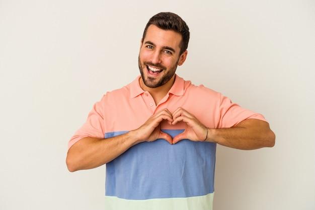웃 고 손으로 심장 모양을 보여주는 흰 벽에 고립 된 젊은 백인 남자.
