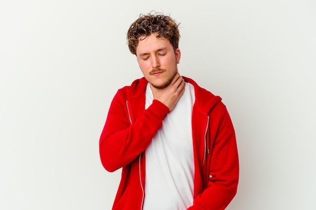 Молодой кавказский мужчина, изолированный на белой стене, страдает от боли в горле из-за вируса или инфекции.