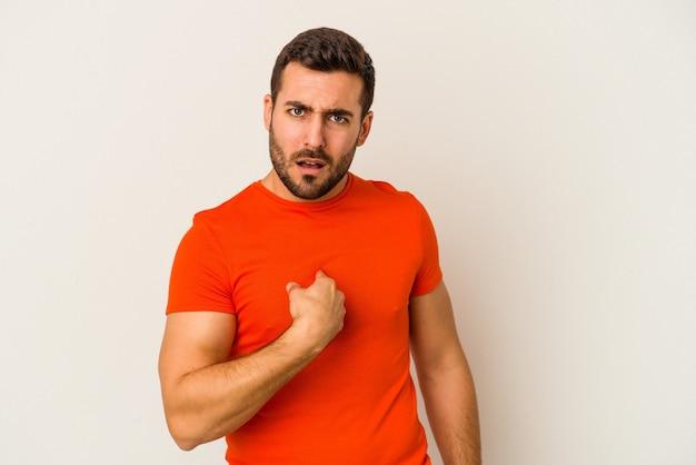 흰 벽에 고립 된 젊은 백인 남자 광범위 하 게 웃 고 손가락으로 가리키는 놀 랐 다.