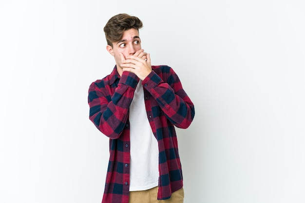 Молодой кавказский человек, изолированные на белой стене, задумчивый глядя на копию пространства, охватывающего рот рукой.