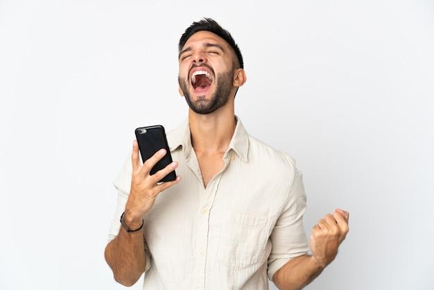 Молодой кавказский человек изолирован на белой стене с помощью мобильного телефона и делает жест победы