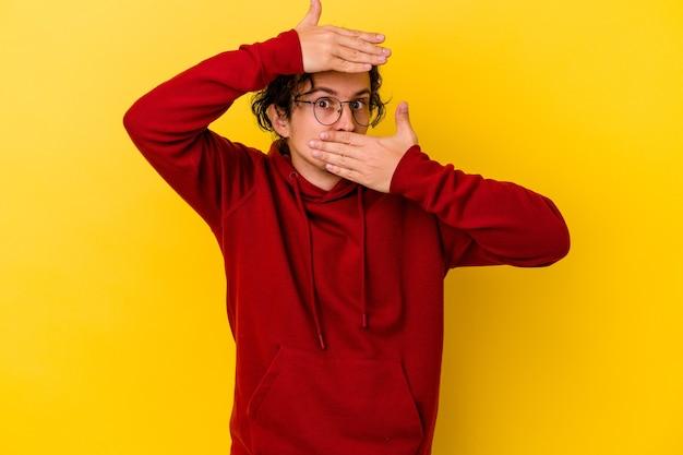 黄色の背景で隔離された若い白人男性は、恥ずかしい顔を覆って、指を通してカメラに点滅します。