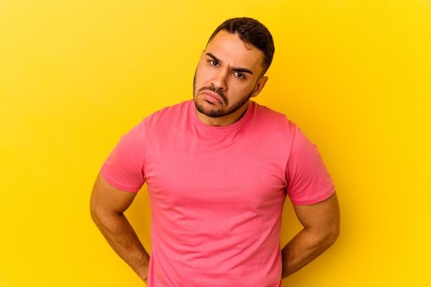黄色の背景に孤立した若い白人男性は頬を吹く、疲れた表情をしています。表情のコンセプト。
