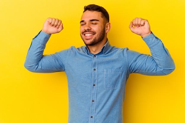 特別な日を祝う黄色の背景に孤立した若い白人男性は、エネルギーでジャンプして腕を上げます。