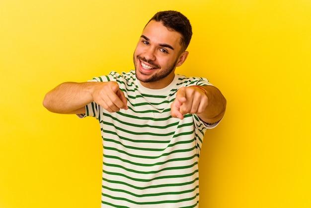 黄色の背景に孤立した若い白人男性は、正面を指している陽気な笑顔。