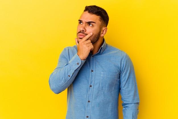 Молодой человек кавказской изолирован на желтом фоне, размышляя, планируя стратегию, думая о способе ведения бизнеса.