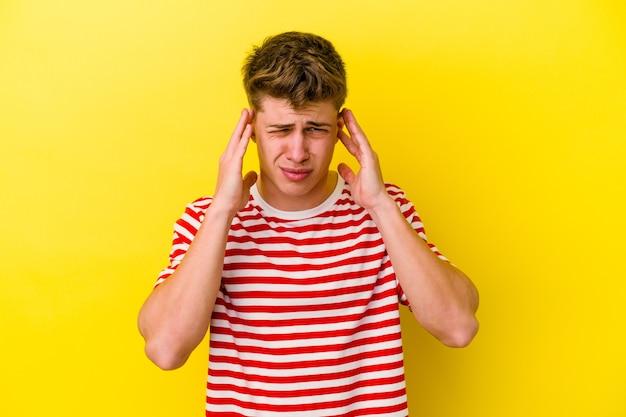 손가락으로 귀를 덮고 노란색 배경에 고립 된 젊은 백인 남자 스트레스와 큰 소리로 주변에 의해 필사적.