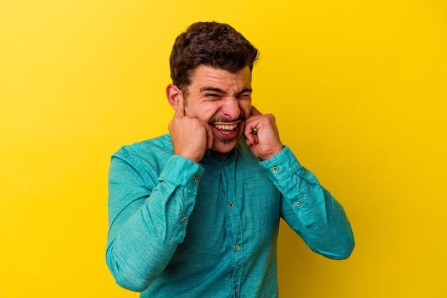 손으로 귀를 덮고 노란색 배경에 고립 된 젊은 백인 남자.