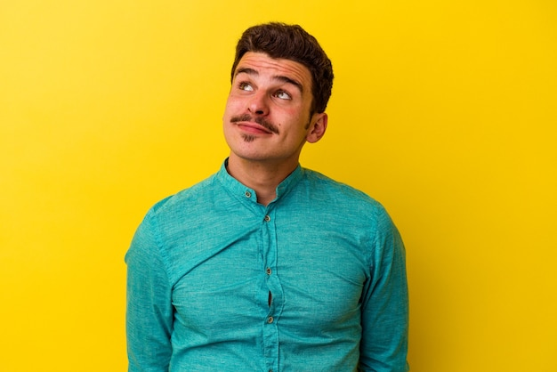 Молодой человек кавказской изолирован на желтом фоне мечтает о достижении целей и задач
