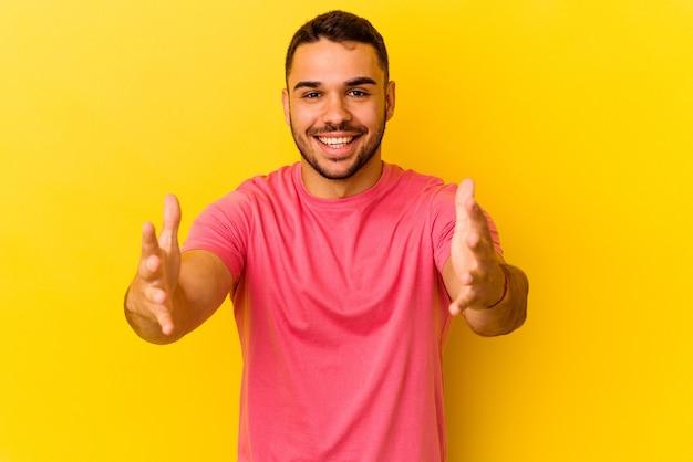 黄色の背景に孤立した若い白人男性は、カメラに抱擁を与えることに自信を持っています。