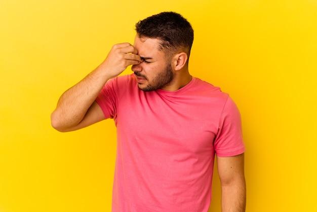 顔の正面に触れて、頭痛を持っている黄色の背景に分離された若い白人男性。