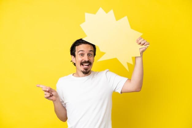 Молодой кавказский человек изолирован на желтом фоне, держа пустой речевой пузырь и указывая сторону