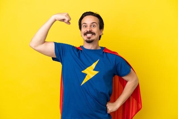 Молодой кавказский мужчина изолирован на желтом фоне в костюме супергероя и делает сильный жест