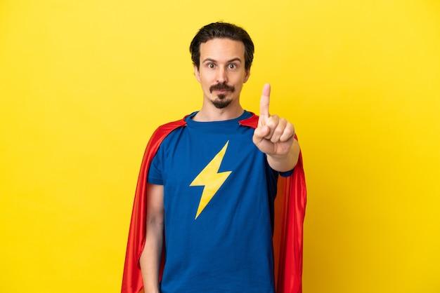 Молодой кавказский мужчина изолирован на желтом фоне в костюме супергероя и указывает вперед
