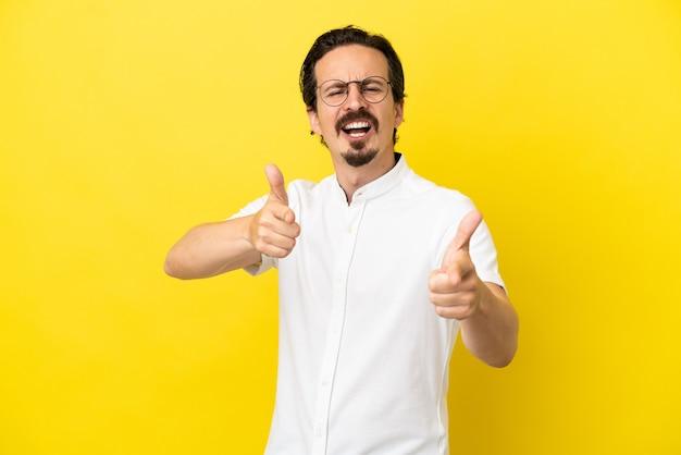 正面を指して笑って黄色の背景に分離された若い白人男性