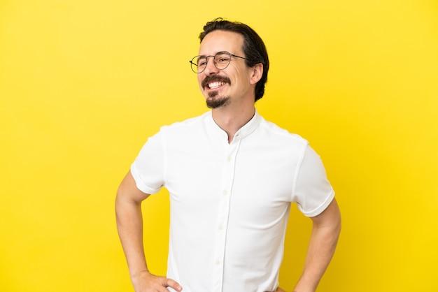 노란색 배경에 고립 된 젊은 백인 남자 엉덩이에 팔을 포즈 하 고 웃 고