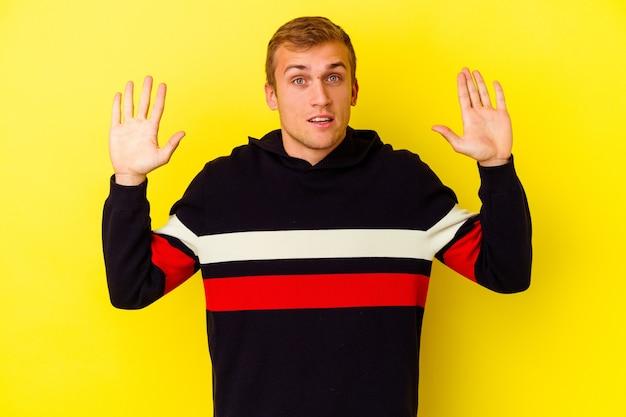즐거운 놀라움을 받고, 흥분하고 손을 올리는 노란색 배경에 고립 된 젊은 백인 남자.