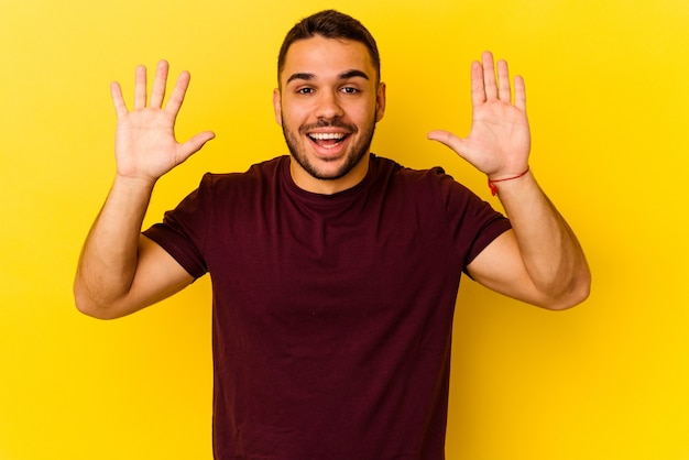 즐거운 놀라움을 받고 흥분하고 손을 올리는 노란색 배경에 고립 된 젊은 백인 남자.