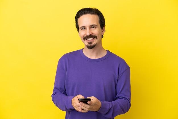 Молодой кавказский человек изолирован на желтом фоне, отправляя сообщение с мобильного телефона