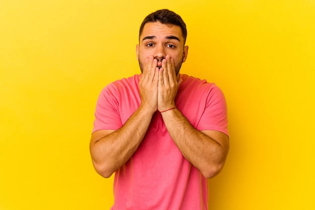黄色の背景に孤立した若い白人男性はショックを受け、手で口を覆い、何か新しいものを発見することを切望していました。