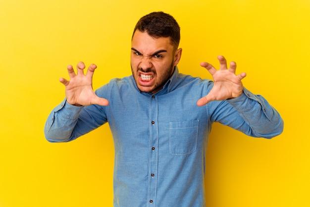 猫を模倣した爪、攻撃的なジェスチャーを示す黄色の背景に分離された若い白人男性。
