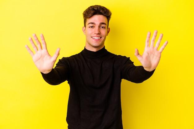 黄色の背景に分離された若い白人男性は、手で10番を示しています。